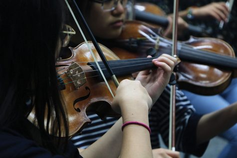 Sophomore Joanna Lee plays the violin during Symphony Orchestra. She said that although her brother was also a musician, orchestra is one way she is able to stand out from her brother who participated in band.