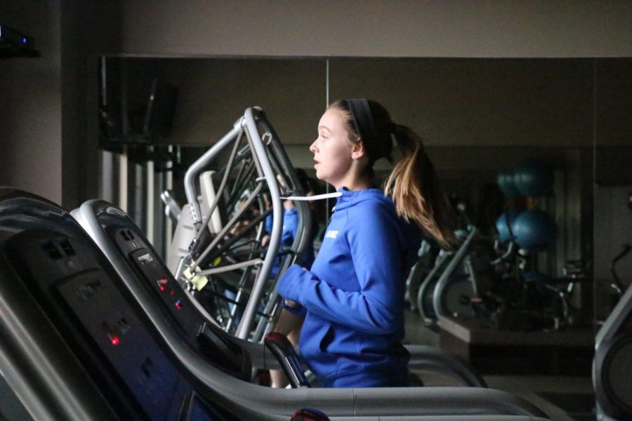 Junior Lindsey Thole runs on a treadmill. Thole typically begins workouts with a walk and then a one or two mile run. She said running helps improve her endurance.