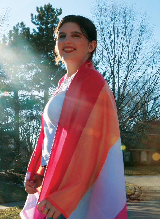 Sophomore Kaylee Gingo smiles with her pride flag. This red, orange, white and pink flag represents lesbian pride. Gingo said she has identified as a part of the LGBTQ+ community since she was a young girl.