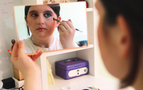 "Sophomore Kaylee Gingo does her makeup in the mirror, incorporating bright colors to show her pride. She said, ""There are some stereotypes that I find in the clothes I wear but otherwise my identity doesn't really affect my expression."