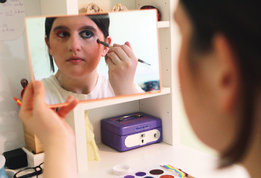 "Sophomore Kaylee Gingo does her makeup in the mirror, incorporating bright colors to show her pride. She said, ""There are some stereotypes that I find in the clothes I wear but otherwise my identity doesn't really affect my expression."""