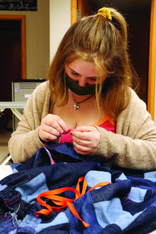 Maddie Kosc  Senior Marissa Cheslock carefully sews flower buttons onto her thrifted pants. She said that 30% of her clothes are altered or thrifted.