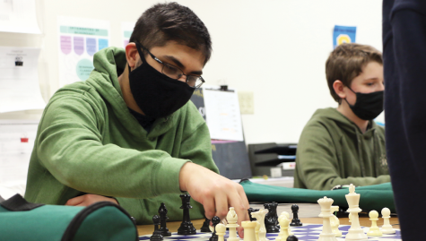 "MAKE A MOVE Akash ""Reno"" Bhowmik, Chess Club co-president and junior, picks up a chess piece to make a move against his opponent during the Feb. 24 meeting in F108. Bhowmik said he values the friendships he is able to enhance through Chess Club meetings."