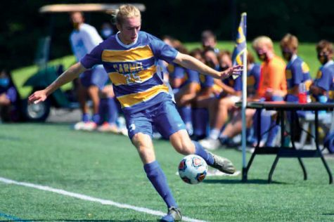 Junior Baenan McKeown kicks a soccer ball during a game. McKeown is a member of the varsity soccer team this year, on top of participating in Ambassadors and taking multiple IB diploma classes and AP courses, and said setting goals helps him manage it all.